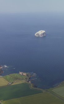 General oblique aerial view centred on the remains of the castle and dovecot with Bass Rock in the distance, taken from the SSE.
