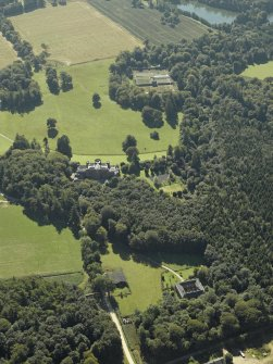 General oblique aerial view centred on the country house with the stable in the foreground and the walled garden in the distance, taken from the N.