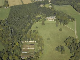 General oblique aerial view centred on the country house with the walled garden in the foreground and the stable in the distance, taken from the SSE.