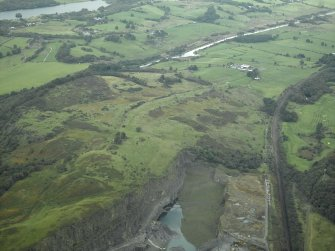 General oblique aerial view centred on the site of the Roman fort and the course of the Antonine Wall with the quarry and canal basin adjacent, taken from the S.