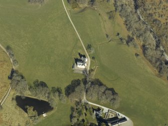 Oblique aerial view centred on the country house, cottage and farmsteading, taken from the SW.