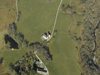Oblique aerial view centred on the country house, cottage and farmsteading, taken from the S.