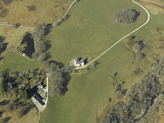 Oblique aerial view centred on the country house, cottage and farmsteading, taken from the SE.
