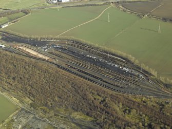 Oblique aerial view centred on railway marshalling yard showing area of former sidings on W side, taken from the SW.
