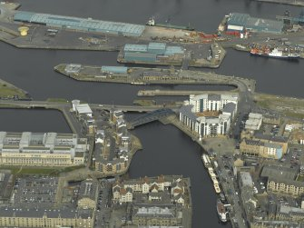 Oblique aerial view centred on the swing bridge, road bridge and office with the harbour, dock and dry dock adjacent, taken from the SW.