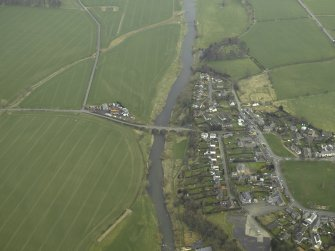 Oblique aerial view centred on northern part of the village and Teviot Bridge, taken from the SW.