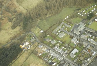 Oblique aerial view centred on station and level crossing site and the NW end of Langholm Street, taken from the S.