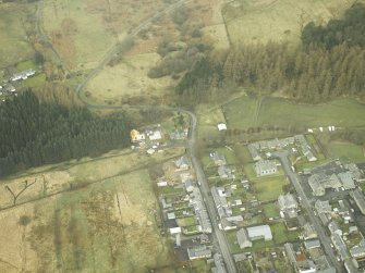 Oblique aerial view centred on station and level crossing site and the NW end of Langholm Street, taken from the SE.
