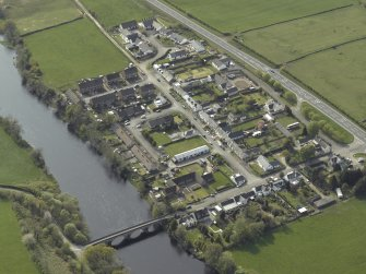 Oblique aerial view centred on the village and road bridge, taken from the E.