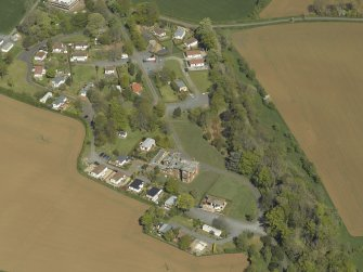 General oblique aerial view centred on the house with caravan park adjacent, taken from the SW.