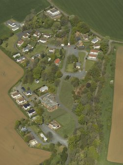 General oblique aerial view centred on the house with caravan park adjacent, taken from the S.