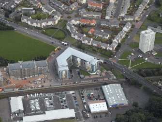 Oblique aerial view centred on Drybrough Crescent showing second phase of new housing development under construction, taken from the NW.