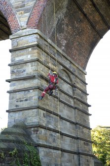 Detail, view from NE,  of drill operator abseiling whilst test drilling lower pier of viaduct.