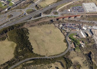 Oblique aerial view centered on the former golf course with the railway viaduct and building adjacent, taken from the E.