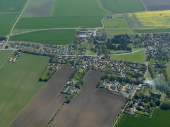 General oblique aerial view centred on the village with the castle adjacent, taken from the NNW.