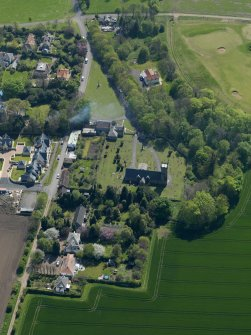 Oblique aerial view centred on the parish church with the church hall adjacent, taken from the N.