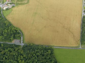 Oblique aerial view centred on the cropmarks of the barrow at Dry Bridge, Islay, taken from the SSE.