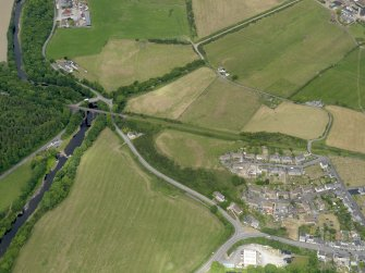Oblique aerial view centred on the parchmarks of the earthwork with the viaduct and the bridge adjacent, taken from the SSE.