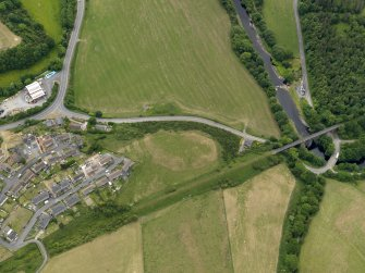 Oblique aerial view centred on the parchmarks of the earthwork with the viaduct and the bridge adjacent, taken from the N.