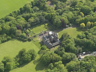 Oblique aerial view centred on the house with the terraced garden adjacent, taken from the NE.