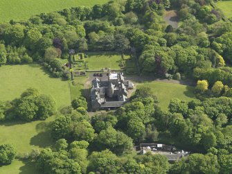 Oblique aerial view centred on the house with the terraced garden adjacent, taken from the N.