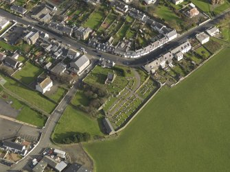 Oblique aerial view centred on the church (s) with the graveyard adjacent, taken from the SW.