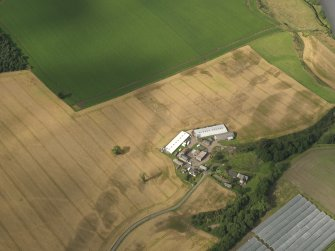 Oblique aerial view centred on the cropmarks of the enclosures, pits, henge, ring ditch and rig, taken from the SW.