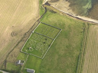 Oblique aerial view centred on the remains of the round church with the burial ground adjacent, taken from the NNW.