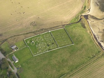 Oblique aerial view centred on the remains of the round church with the burial ground adjacent, taken from the WNW.