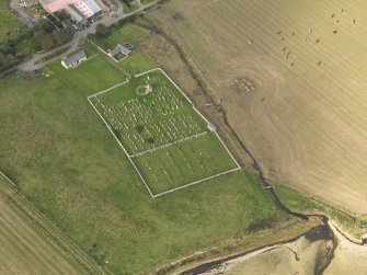 Oblique aerial view centred on the remains of the round church with the burial ground adjacent, taken from the SSW.