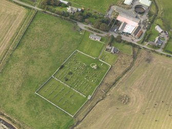 Oblique aerial view centred on the remains of the round church with the burial ground adjacent, taken from the SSE.