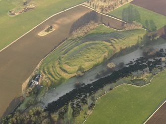 Oblique aerial view centred on the remains of the fort with the farmstead adjacent, taken from the SSW