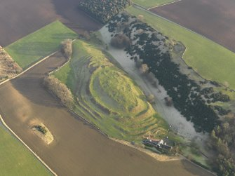 Oblique aerial view centred on the remains of the fort with the farmstead adjacent, taken from the NW.