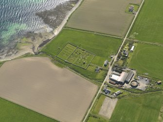 Oblique aerial view centred on St Nicholas' Church, Orphir with Bu of Orphir farmstead adjacent, taken from the NE.