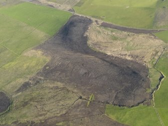 Oblique aerial view centred on the remains of the round house, enclosure and field banks on the summit of Billia Fiold, taken from the SSW.