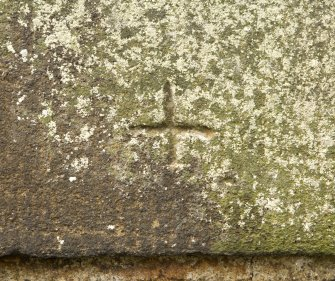 Detail of possible masons mark in form of small 'cross' on S side parapet.