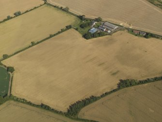 Oblique aerial view of the cropmarks of the round house, pits and possible souterrain with Hoprig Mains, taken from the WNW.