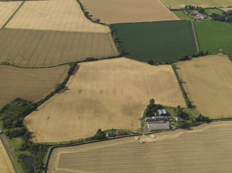 General oblique aerial view of the cropmarks of the round house, pits and possible souterrain with Hoprig Mains, taken from the S.