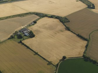 Oblique aerial view of the cropmarks of the round house, pits and possible souterrain with Hoprig Mains, taken from the N.