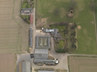 Oblique aerial view centred on the remains of the tower-house with the farmstead adjacent, taken from the NNW.