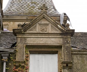 Detail of dormer with carved thistle motif in the pediment and finial.