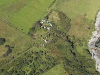 Oblique aerial view centred on the two farmsteads and site of the chapel (in the centre top), taken from the SE.