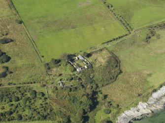 Oblique aerial view centred on the two farmsteads and the site of the chapel (middle right), taken from the ESE.