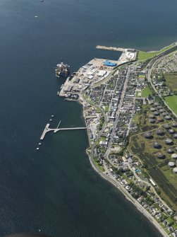 Oblique aerial view of Invergordon centred on the naval dockyard and harbour, taken from the NE.