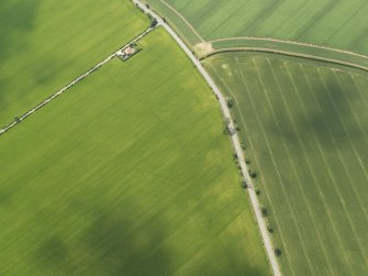 Oblique aerial view centred on the cropmarks of the round house and pits, taken from the NNE.