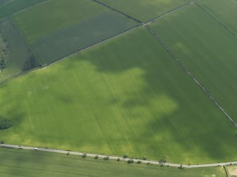 Oblique aerial view centred on the cropmarks of the round house and pits, taken from the WNW.