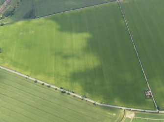 Oblique aerial view centred on the cropmarks of the round house and pits, taken from the W.