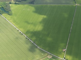Oblique aerial view centred on the cropmarks of the round house and pits, taken from the WSW.