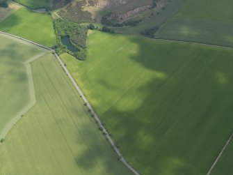Oblique aerial view centred on the cropmarks of the round house and pits, taken from the SW.