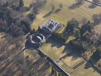 Oblique aerial view centred on the country house with the stable block adjacent, taken from the NW.